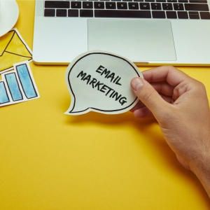 """cropped image of man holding speech bubble with""""email marketing"""" lettering near laptop"""